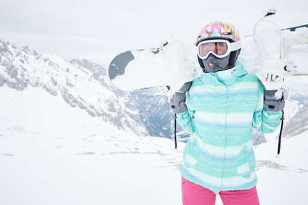 Female snowboarder wearing colorful helmet, blue jacket, grey gloves and pink pants standing standing with snowboard in her hands and preparing for ride - snowboarding concept, copy space 版權商用圖片