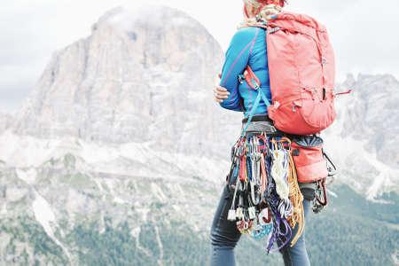 Bergsteigerin mit handwerklichem Klettergerüst inklusive Rucksack, Helm, Chalkbag, Gurtzeug mit federbelasteten Nocken, Muttern, Quickdraws, Schlingen und Karabinern zur Vorbereitung auf den Aufstieg im Sommer Dolomiten Standard-Bild