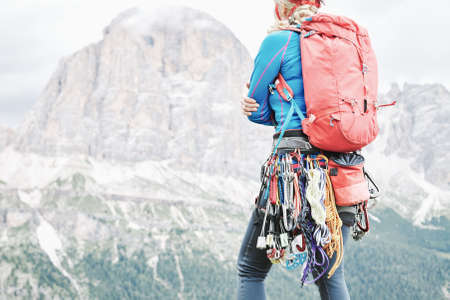 Female mountaineer with trad climbing rack including backpack, helmet, chalk bag, harness with spring-loaded cams, nuts, quickdraws, slings and carabiners preparing for ascent in summer Dolomite Alps