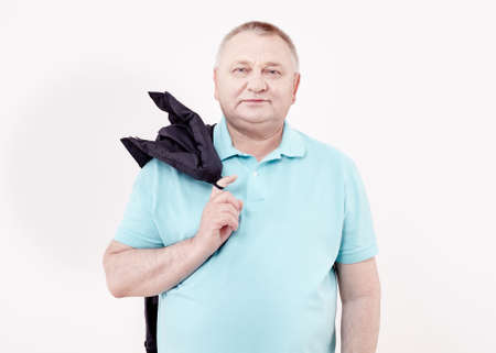 Mature cheerful man wearing blue shirt holding jacket over his shoulder and smiling against white wall - casual dress code concept Foto de archivo