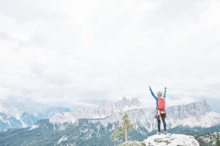 Female mountaineer with backpack, helmet and harness with climbing gear raising her hands celebrating successful climb during summer day in Dolomite Alps - mountaineering or sport climbing concept 스톡 콘텐츠