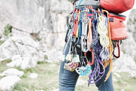 Close-up of mountaineer with trad climbing rack including backpack, chalk bag, harness with spring-loaded cams, nuts, quickdraws, slings and carabiners preparing for ascent in summer mountains