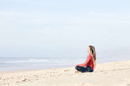 Young adult surfer with dreadlocks wearing wetsuit sitting cross-legged on beach near spot and meditating before summer evening surfing session - harmony, yoga, surfing concept, copy space, Portugal