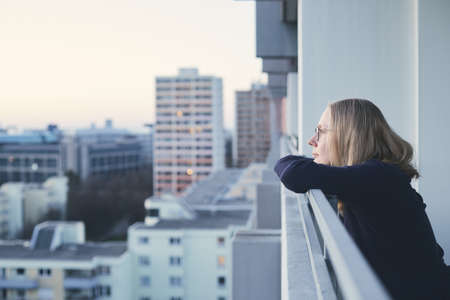 Mood portrait of young blonde woman wearing glasses enjoying urban sunset on balcony - women dream concept