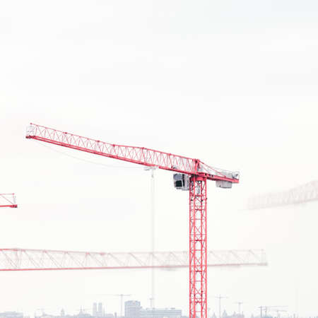 Operating tower cranes against cityscape - construction and minimalism concept Stock Photo