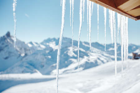 Icicles hanging from roof of mountain hut against winter snowy landscape of ski resort in French Alps - winter holidays background concept
