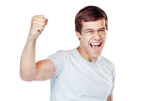 Young man wearing glasses and blue t-shirt standing and happy screaming celebrating win with raised fist isolated on white background - sports fan support or success concept
