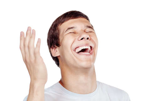 Close up of young man laughing out loud with closed eyes and hand near his head - laughter is best medicine concept