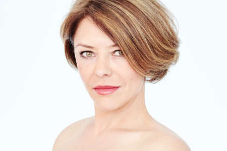 Close up portrait of beautiful middle aged woman with short brown hair, fresh makeup, naked shoulders and neck over white background - mature beauty, skin care or anti age concept 免版税图像 - 111974624
