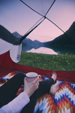 Tourist woman sitting in tent with mug in hand enjoying beautiful view to summer mountain lake at sunset - camping, hiking and travel concept Stock Photo