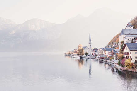 Stunning autumn view to sunny and calm Hallstatt village on idyllic Hallstatter lake in Austrian Alps, Salzkammergut region, Austria - travel, vacation or holiday concept