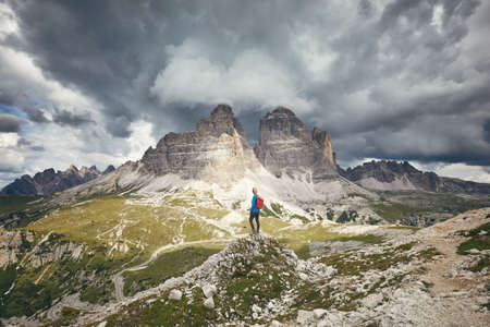 Female hiker with red backpack enjoying stunning view to Tre Cime di Lavaredo (Drei Zinnen) under heavy clouds from hiking trail during hike in Dolomites, Italy - adventure, travel and trekking