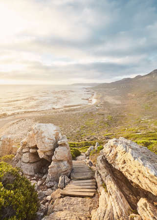 Stunning view through boulders and wooden footpath to ocean and mountains on golden sunset near Cape of Good Hope, South Africa 写真素材