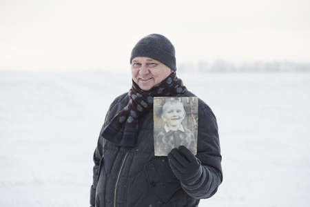 Senior man wearing knit cap, scarf, jacket and leather gloves smiling and showing his picture as child standing in winter field - memory concept