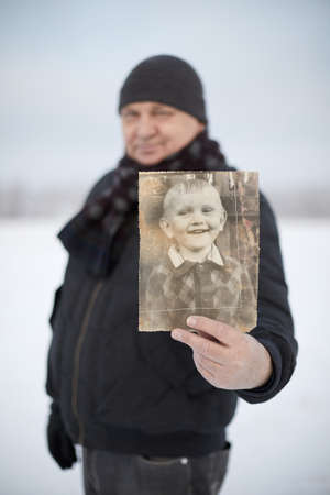 Senior man wearing knit cap, scarf, jacket and leather gloves smiling and showing his picture as child standing in winter field - memory concept, focus on picture Stock Photo