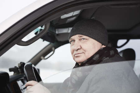 Portrait of senior man wearing knit cap, scarf, jacket sitting behind wheel of his car and looking through window - winter driving or mature drivers concept Stock Photo