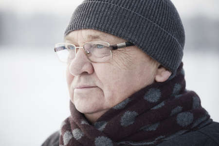 Close up portrait of senior man wearing glasses, knit cap and scarf standing outdoors in winter Stock Photo