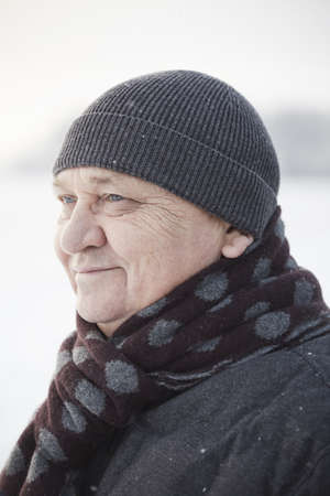 Close up portrait of smiling senior man wearing knit cap, scarf and jacket standing outdoors in winter Stock Photo