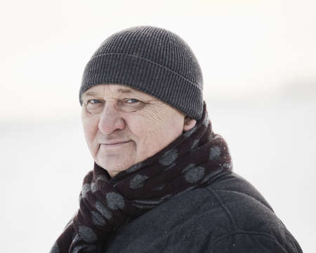 Portrait of senior man wearing knit cap, scarf and jacket standing in winter field during snowfall 写真素材