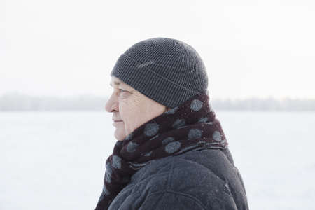 Profile portrait of senior man wearing knit cap, scarf and jacket standing in winter field during snowfall 写真素材