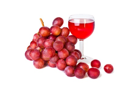 Bunch of red grapes with a glass of wine on a white background photo