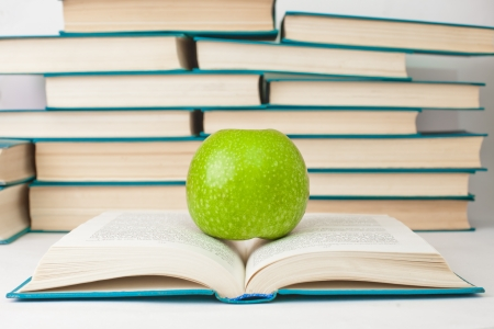 Green apple lying on an open book