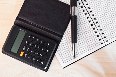 Calculator with notepad and pen on the table photo