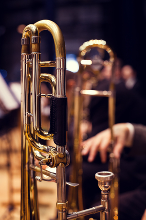 Trombones in the hands of musicians on stage photo