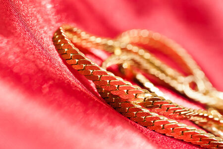 Gold chain on red cloth closeup photo