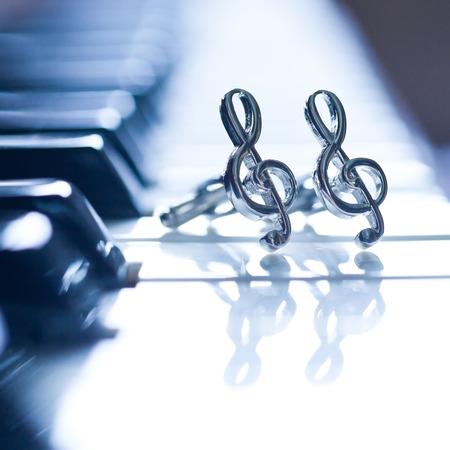 Ornaments In The Form Of A Treble Clef On Piano Keyboard Stock Photo