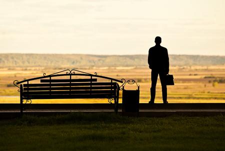hombre pensando: Silueta de un hombre con un malet�n cerca de los bancos en el parque