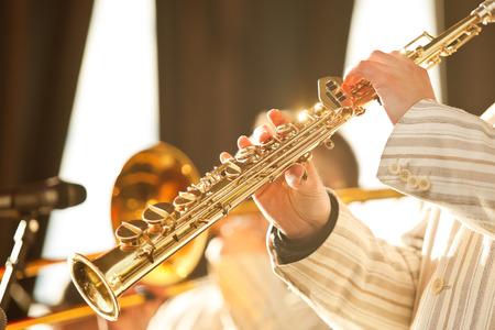 soprano saxophone: Manos del músico tocando el saxofón soprano en la luz del sol de oro