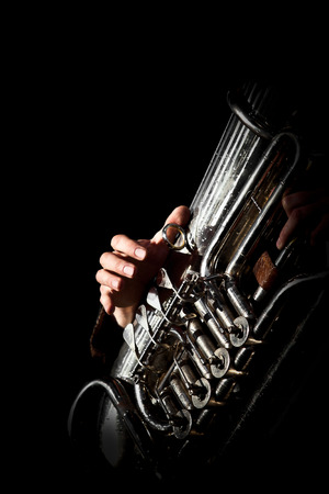 trumpet: Hand of the person playing the tuba in dark colors  Stock Photo