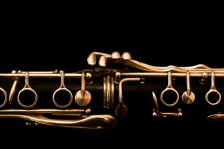 Detail of the clarinet in golden tones on a black background Stock Photo