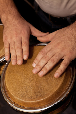 to pulsate: Hands of man playing the bongos Stock Photo