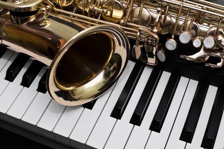 ピアノのキーの上に横たわるサックスのフラグメント 写真素材
