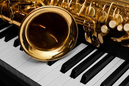 Fragment van de saxofoon liggend op de pianotoetsen Stockfoto