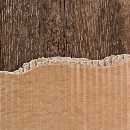 torn cardboard: Torn cardboard packaging on a wooden surface as a background