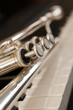 Detail of trumpet lying on the piano keys Stok Fotoğraf