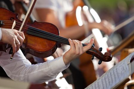 orquesta clasica: Viol�n en manos de un m�sico en el primer orquesta Foto de archivo