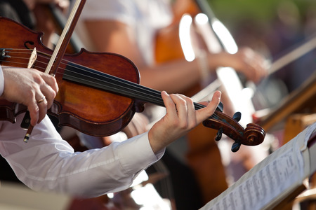 Viool in de handen van een muzikant in het orkest close-up