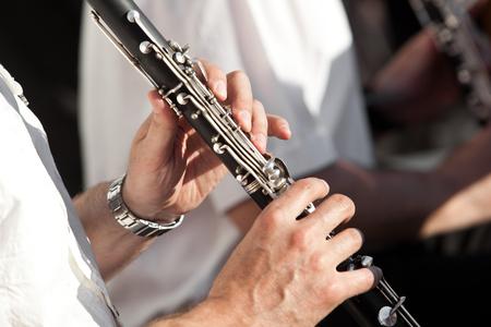 Menselijke handen spelen van een klarinet close-up