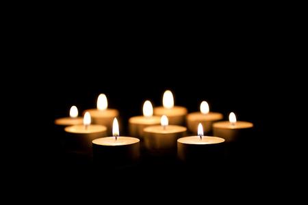 candela: Candele accese su uno sfondo nero Archivio Fotografico