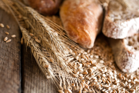 Rye spikes and bread on a wooden surface closeup Reklamní fotografie