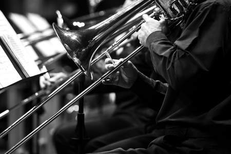 Trombones in the hands of the musicians in the orchestra in black and white