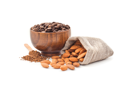 Coffee beans in a wooden cup with almonds on a white background Stock Photo