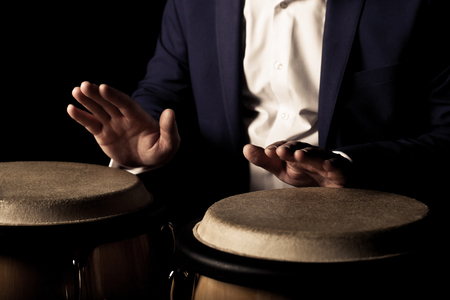 Hands of a musician playing on bongs in dark tones