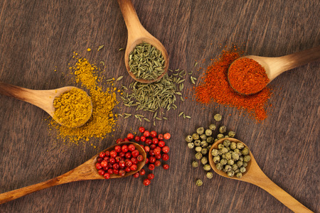 Different spices on a wooden surface