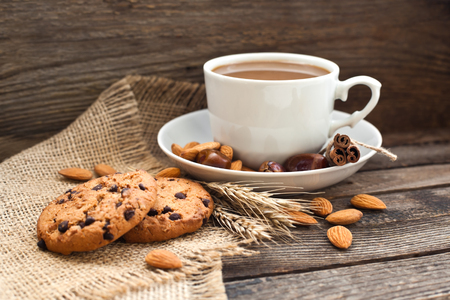 Coffee in a cup with cookies and nuts