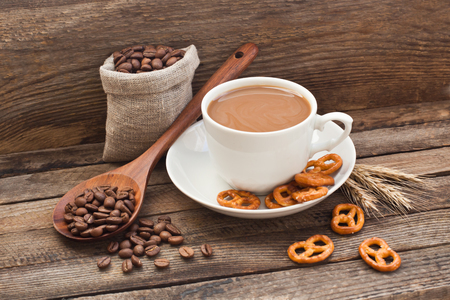 Coffee in a cup with coffee beans and cracker on a wooden background